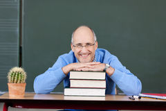 Friendly male teacher relaxing. In the classroom in front of the blackboard Stock Images