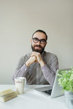 Friendly man with beard in glasses looking at camera over laptop Royalty Free Stock Image