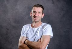 Friendly man with crossed arms in front of gray background Stock Photography