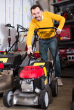 Friendly man deciding on best lawnmower in garden equipment shop Royalty Free Stock Photos