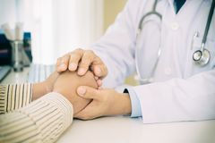 Friendly man doctor hands holding patient hand sitting at the de stock image