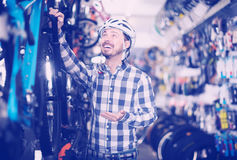 Friendly man in helmet chooses for himself sports bike in bicycl Royalty Free Stock Image