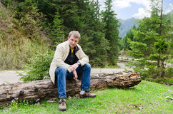 Friendly man sitting on a tree Royalty Free Stock Photography