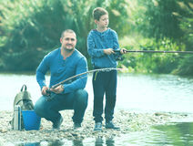Friendly man and son fishing with rods Royalty Free Stock Photography