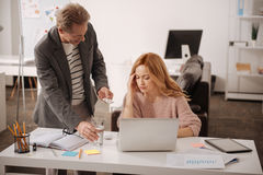 Friendly man taking care of ill colleague in the office. May I help you. Smiling helpful mature men standing in the office and expressing joy while offering Royalty Free Stock Photos