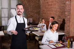 Friendly man waiter demonstrating country restaurant. Friendly men waiter demonstrating country restaurant to visitors Stock Photography