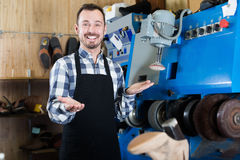 Friendly man worker displaying his workplace. And tools in shoe repair workshop Royalty Free Stock Images