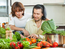 Friendly married couple preparing vegetable salad. In my house Stock Images