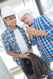 Friendly master electrician and apprentice working with loads wiring Stock Images