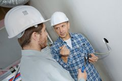 Friendly master electrician and apprentice working stock photos
