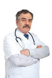 Friendly mature doctor man. Standing with arms folded isolated on white background stock images