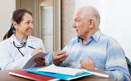 Friendly mature doctor talks with  senior man Royalty Free Stock Images