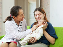 Friendly mature pediatrician doctor examining newborn Stock Photos
