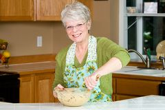Friendly, mature woman. A friendly, gray haired mature woman baking cookies Stock Photos