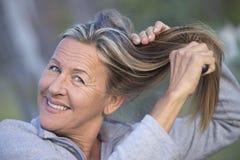 Friendly mature Woman brushing hair outdoor Stock Photos