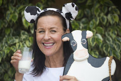 Friendly mature woman with milksop and cow Royalty Free Stock Image