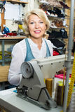 Friendly mature woman tailor using sewing machine Royalty Free Stock Image