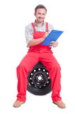 Friendly mechanic holding clipboard and sitting on tire Royalty Free Stock Images