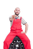 Friendly mechanic offering or giving car key Royalty Free Stock Image