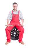 Friendly mechanic sitting on car wheel Royalty Free Stock Images
