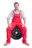 Friendly mechanic sitting on car wheel tire Royalty Free Stock Images