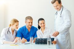 Friendly medical coworkers chatting over illness of patient stock photography