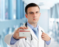 Friendly medical doctor with blank card (badge). Stock Photos