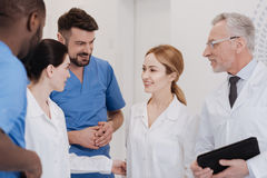 Friendly medical team meeting new colleague in the clinic stock photo
