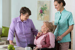 Friendly meeting. Two older women and young pretty nurse on friendly meeting Royalty Free Stock Photo