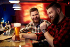 Friendly men. Friendly young men with beer talking in pub Royalty Free Stock Photo