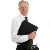 Friendly middle-aged business executive. In his shirtsleeves smiling at the camera with a leather portfolio under his arm Royalty Free Stock Photo