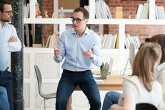 Friendly middle aged team leader instructing employees. Friendly middle aged team leader, boss, executive instructing employees at briefing, making presentation royalty free stock image