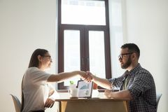 Friendly millennial coworkers handshaking over office desk. Busi. Friendly millennial businessman and businesswoman handshaking over office table after pleasant Stock Photos