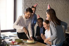 Friendly multi-ethnic employees cutting cake celebrating birthda. Friendly multi-ethnic employees in party hats cutting cake celebrating excited colleague happy stock photography