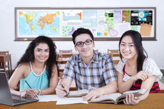 Friendly multi ethnic students studying in the class. Group of three mixed race student studying together in the class and smiling at the camera Stock Image