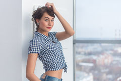 Friendly nice relaxed girl posing in modern light studio wearing trendy casual outfit, touching hair with her hand. Smiling royalty free stock photos