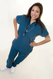 Friendly nurse. Full body of an attractive young brunette Hispanic woman health care worker standing with hands on hips with a smiling friendly expression Royalty Free Stock Images