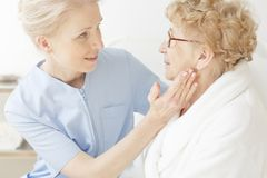 Friendly nurse comforting elderly woman Royalty Free Stock Photography