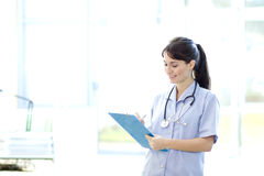 Friendly nurse holding clipboard Stock Image