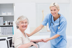 Friendly nurse holding senior patients hand Stock Image