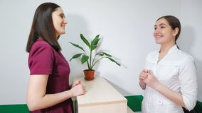 Friendly nurse on reception is talking with patient young woman, side view. royalty free stock photography