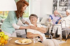 Friendly nurse supporting smiling senior woman in nursing house. Friendly nurse supporting smiling senior women in nursing house. Blurred background stock photography