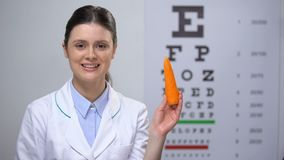 Friendly oculist recommending carrot for maintaining good vision, healthy food. Stock footage stock video