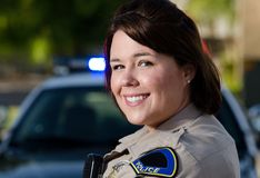 Friendly officer. A smiling officer shows she is ready to help out Stock Photo