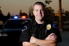 Friendly officer. A smiling police officer with his arms crossed in front of his patrol car Stock Photos