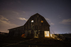 Friendly old barn. An old hay barn warmly lit through the cracks on the inside stock photo