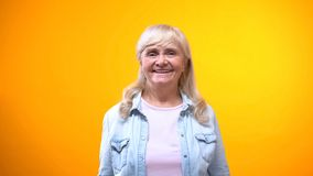 Friendly old lady smiling on camera, concept of satisfied customer, good service. Stock photo royalty free stock images