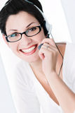 Friendly Operator. Beautiful young woman with charming big green eyes is bearing modern glasses and receiving calls on a headset Stock Photography