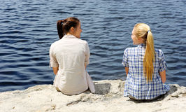 Friendly outdoor girls. Two friends sit near the lake and enjoy an afternoon outdoors together royalty free stock photography