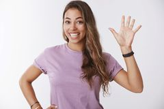 Friendly outgoing sound-minded cute energized sporty girl raising head volunteering wanna help waving raised hand. Smiling broadly cheering happily greeting royalty free stock image